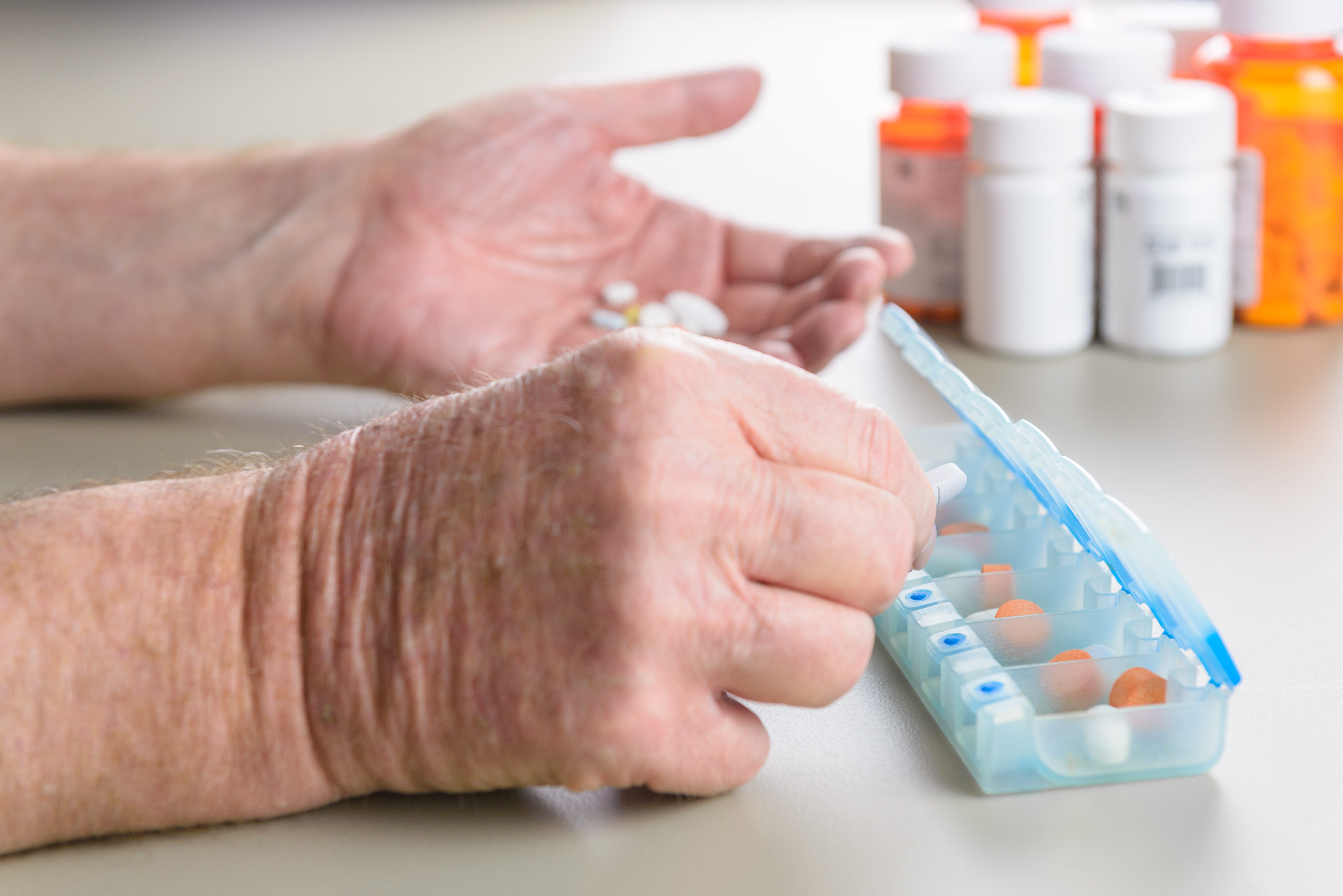 Elderly man sorts medications